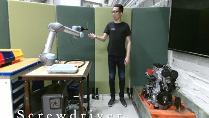 KTH researcher Hongyi Liu tests a robot arm by placing his hand in its path.